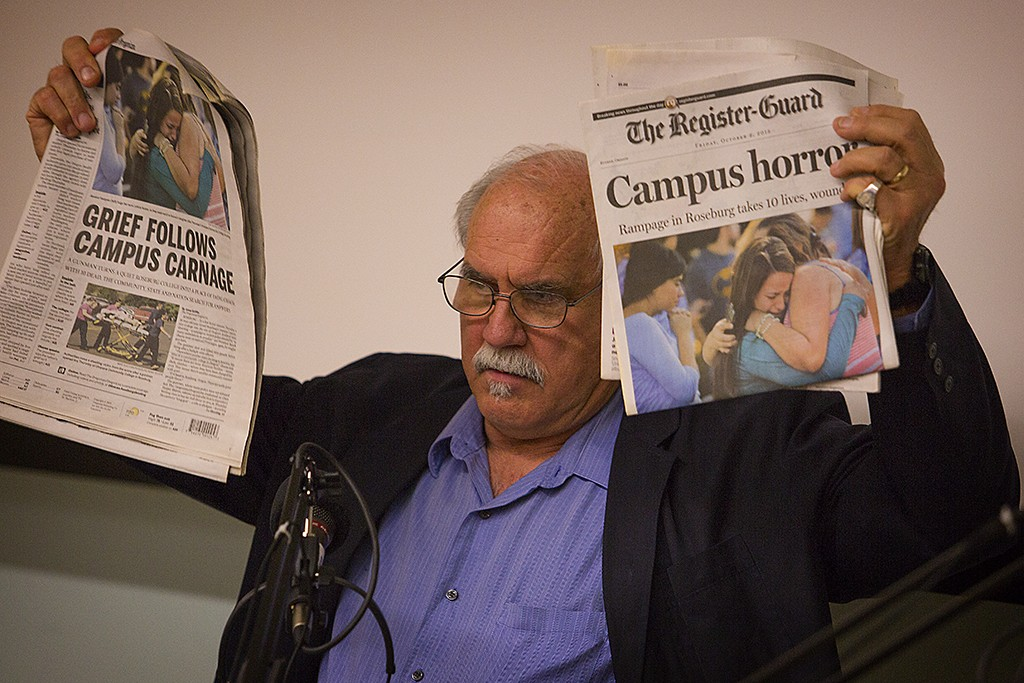 UO professor and photojournalist Dan Morrison holds up copies of The Oregonian and The Register-Guard from the day following the UCC shooting.