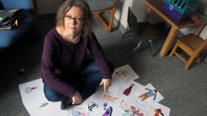 Marjorie Taylor sits amid creative work by 8- to 10-year olds.