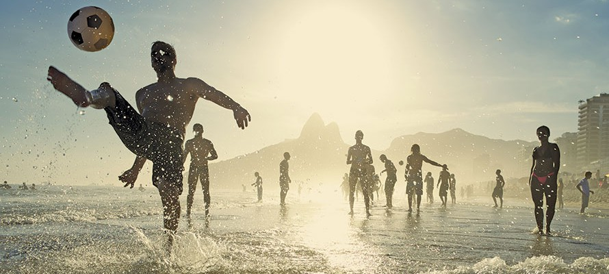 Image of people playing soccer on the beach