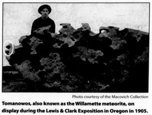 "Photograph of a man standing next to the meteorite, which is almost as tall as he is. Caption reads: ""Tomanowos, also known as the Willamette meteorite, on display during the Lewis and Clark Exposition in Oregon in 1905."" Photo courtesy of the Macovich Collection."