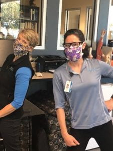 Two women wearing cloth masks in an office