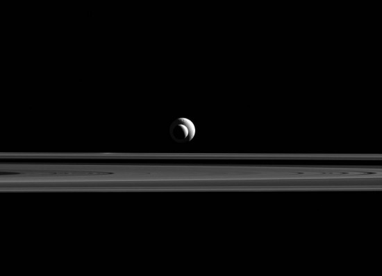 Saturn's moons Tethys and Enceladus lined up with rings of Saturn in foreground.