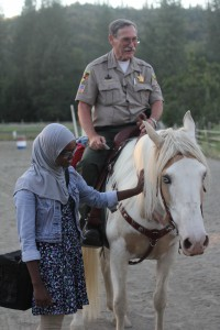 Journalism student Fahmo Mohammed gets to know Josephine County Sheriff Gil Gilbertson and his horse on a shoot in Grants Pass, Oregon.