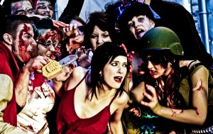 """An image from graduate student Bryce Peake's photo-ethnographic research on the Toronto Zombie Walk. His photo """"Red Dress Critique"""" depicts a critical performance against 'victim' representations of women in horror films, and is from his Master's research on the implications of trance-states on imaginative forms of social activism."""