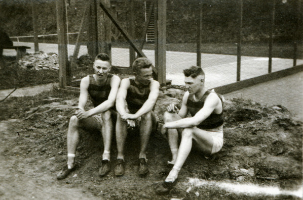 Black and white photo of three unidentified track athletes seated at the side of a track in 1915.