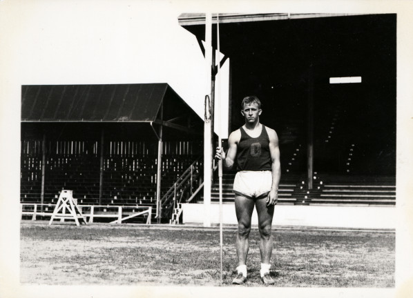 Black and white photo of University of Oregon javelin thrower Bob Parke, with a javelin by is side, taken at Hayward Field during the mid-1930s.