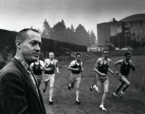 Black and white photo of University of Oregon track coach Bill Bowerman watching as five distance runners enter a turn on the practice track near Hayward Field in 1959. From left to right: Mark Robbins (face blocked by Bowerman), Phil Knight, Wilcey Winchell, Dick Miller, and an unidentified athlete. Picture appears on page 244 of the 1960 Oregana.