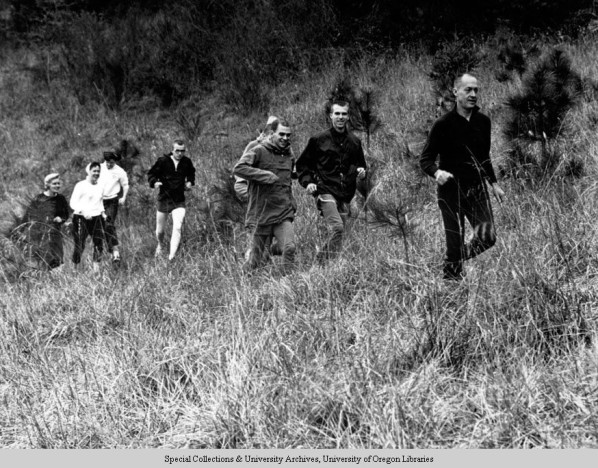 Black and white photo of University of Oregon track coach Bill Bowerman leading a group of joggers on a hillside near his home outside of Springfield in 1964. The two women at the back of the group are Barbara Bowerman (left) and Robin Jaqua. Picture appears in Bowerman and the men of Oregon, by Kenny More, 2006.