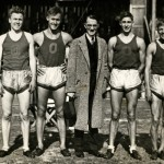 Black and white photo of the 1934 University of Oregon mile relay team flanking University President C. V. Boyer, after winning the Northwest Conference championship at Hayward Field. From left to right: Sherwood Burr, Bill Bowerman, Boyer, George Scharpf, and Howard Patterson.