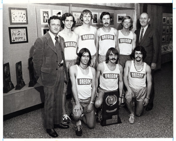 Black and white photo of the 1973 NCAA champion University of Oregon men's cross country team taken inside McArthur Court. Standing, from left to right: Coach Bill Dellinger, Dave Taylor, Gary Barger, Randy James, Scott Daggatt, Coach Bill Bowerman. Kneeling, l-r: Terry Williams, Steve Prefontaine, Tom Hale.