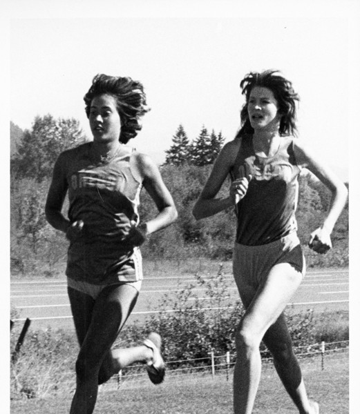 Black and white photo of University of Oregon cross country runners Eryn Forbes (left) and Jody Parker (right) in action at the 1979 Garrie Franklin Classic near Lane Community College. Forbes finished the race in eighth place and Parker in tenth.