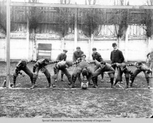Black and white photo of the 1899 University of Oregon football team in a posed picture taken at Multnomah Field in Portland, showing the offense ready to snap the ball.