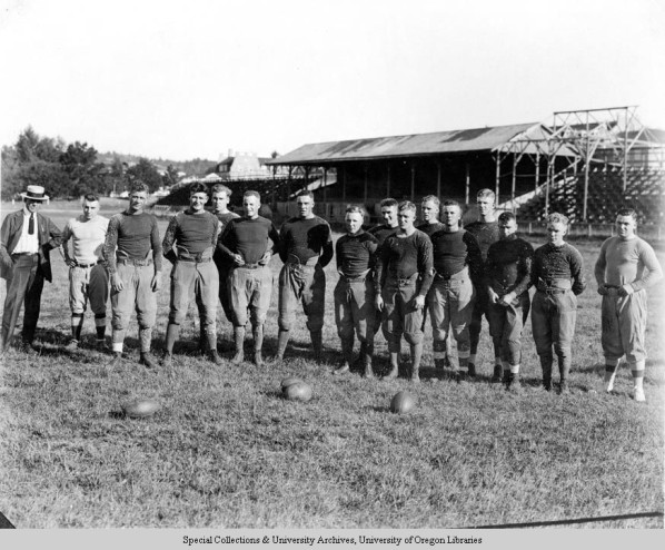 """Black and white photo of members of the 1920 University of Oregon football team taken at the first practice of the season on September 15 at Hayward Field. Trainer Bill Hayward is at far left and next to him is head coach """"Shy"""" Huntington. Also identifiable is George King (8th from left). Picture appears on page 133 of the 1921 Oregana."""