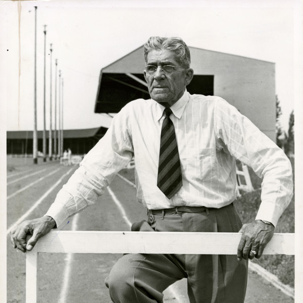 Black and white image of Bill Hayward leaning against a hurdle on the track.