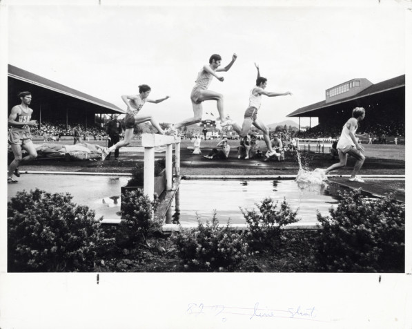 Black and white photo of runners at the water jump during the 3000 meter steeplechase at the 1971 AAU Championships held June 25-26 at Hayward Field. Mike Manley won, representing the Oregon Track Club. Identifiable are Steve Savage (2nd from left) and Barry Brown (4th from left).