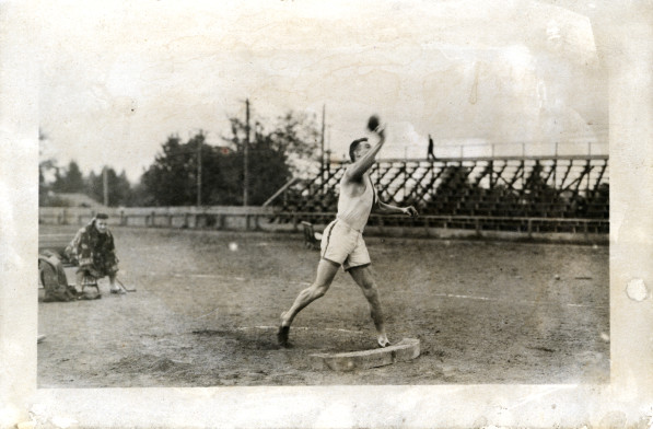 Black and white photo of an unidentified University of Oregon shot putter in action during a 1913 practice at Kincaid Field.