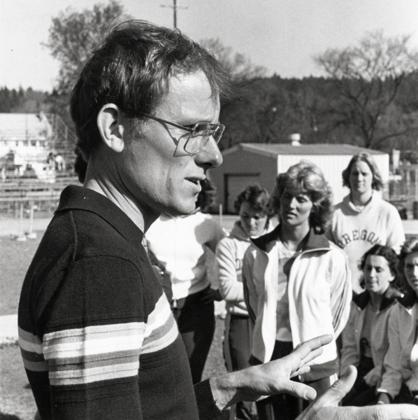 Black and white photo of University of Oregon women's track and field coach Tom Heinonen addressing the team at Hayward Field. Heinonen served as U of O track coach from 1975-2003.