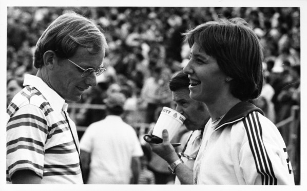 Black and white photo of University of Oregon head women's track coach Tom Heinonen and runner Ellen Schmidt at a meet held in Corvallis in the late 1970s or early 1980s.