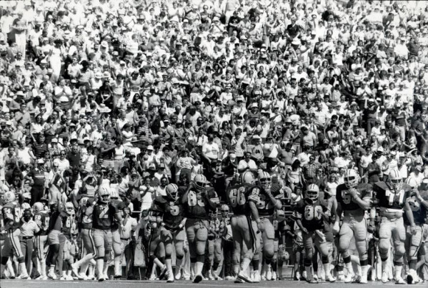 Black and white photo of University of Oregon football players entering the playing field from the sideline during a game played at Autzen Stadium during the early 1980s.