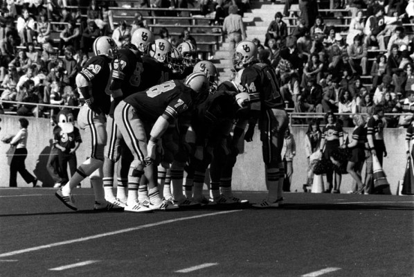 Black and white photo of University of Oregon quarterback Dan Daly (#14) calling a play in the huddle during a game played at Autzen Stadium in 1978.