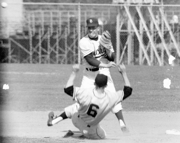"""Black and white photo of University of Oregon middle infielder Eugene """"Wimp"""" Hastings after making the relay throw to first as part of a double play, while an opposing base runner bears down on him, during a game played at Howe Field during the late 1950s."""