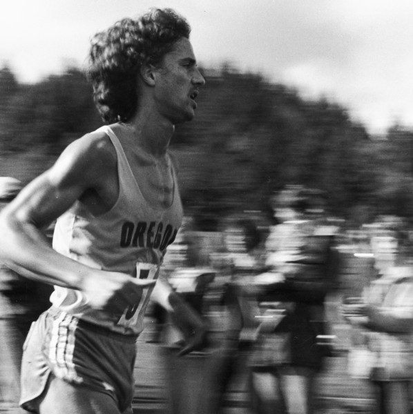 Black and white photo of University of Oregon cross country runner Ken Martin running the track at the 1979 Northern Division Championships held at Lane Community College.