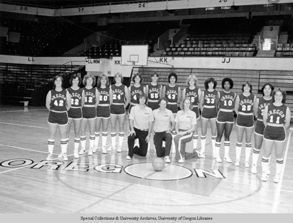 Black and white photo of the 1979-80 University of Oregon women's basketball team taken at McArthur Court. From left to right, standing: Cindy Anderson, Suzanne Washington, Debbie Ware, Beth Busby, Bev Smith, Meg Jones, Joni Martin, Claudia Eaton, Kris Luedloff, Mary Ann Stoican, Debbie Adams, Julie Cushing, Andrea Drake, and Allison Towriss. Kneeling: assistant coach Neil Stenseth, head coach Elwin Heiny, and assistant coach Sheila Strike.
