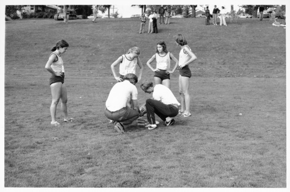 Black and white photo of University of Oregon cross country runners, from left to right, Jennifer Daniell, Heather Tolford, Jenifer Bates and Ellen Schmidt, standing, as Coach Tom Heinonen and an unidentified man crouch, attending to something during the late 1970s.