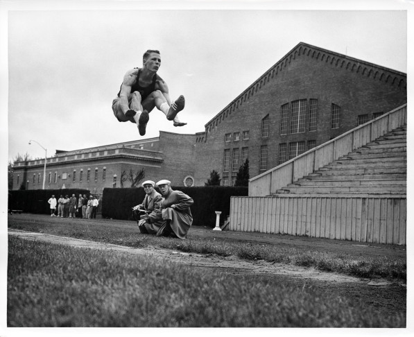 "Black and white photo of University of Oregon broad jumper Martin Pedigo in mid-air, on his way to a first place finish at the Northern Division Meet held at Pullman, Washington in 1957. Pedigo's jump of 25'2"" was a new personal best, and a new school record."