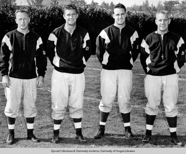 Black and white photo of the 1952 University of Oregon football coaching staff taken near Hayward Field. From left to right: John McKay, Jack Roche, Vern Sterling, and head coach Len Casanova.