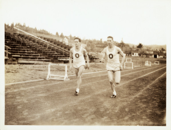 Black and white photo of two unidentified University of Oregon track athletes running at Hayward Field during the 1920s.