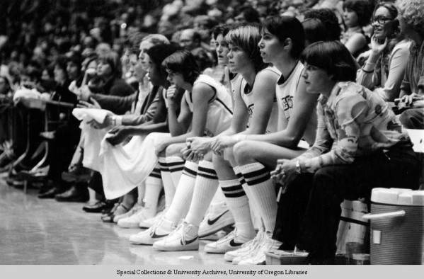 Black and white photo of the University of Oregon women's bench during an exhibition basketball game against the Soviet Union's national team at McArthur Court on December 3, 1979, and won by the Soviets 131-53. Identifiable are Joni Martin (2nd from right) and Bev Smith (3rd from right).