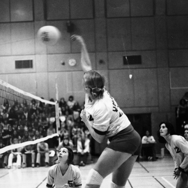 Black and white photo of an unidentified Duck volleyball player leaping to hit the ball during a game played in the women's gym in Gerlinger Annex on November 12, 1977.