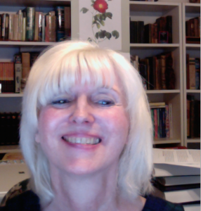 Cynthia M. Vakareliyska smiles into the camera in front of a bookcase