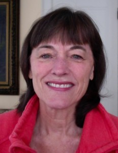 An image of Stephanie Wood facing the camera, wearing a red sweater, and smiling