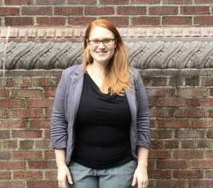 Rachel Rochester stands in front of a brick wall and smiles at the camera