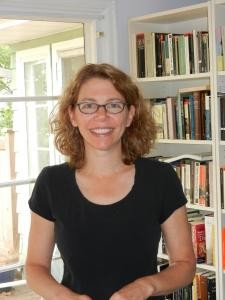 An image of Heidi Kaufman standing in front of a bookshelf facing the camera
