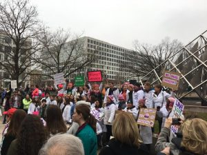An image of women holding signs and wearing lab coats in DC against a gray sky.