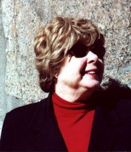 A picture of Marjorie Perloff, smiling, wearing dark sunglasses, a red turtleneck, and a black blazer