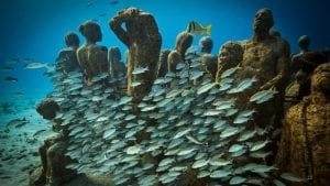 A series of statues sitting on the ocean floor surrounded by fish