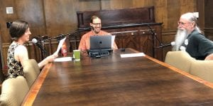 Three scholars sitting around a wood table recording a podcast