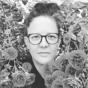 A close-up of Lisa Fink's face, wearing glasses, and surrounded closely by flowers. Black and white.