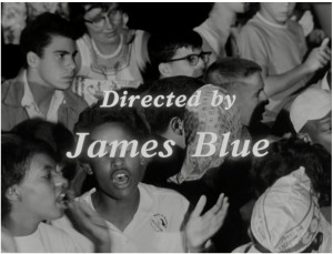 A screen shot of James Blue's opening film shot of the March showing a group of people clapping
