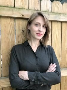 Lindsey Mazurek standing again a wall wearing a black shirt and smiling