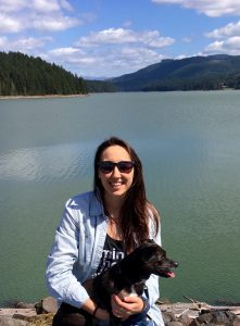 Photo of Lacey Guest with her dog in front of a lake