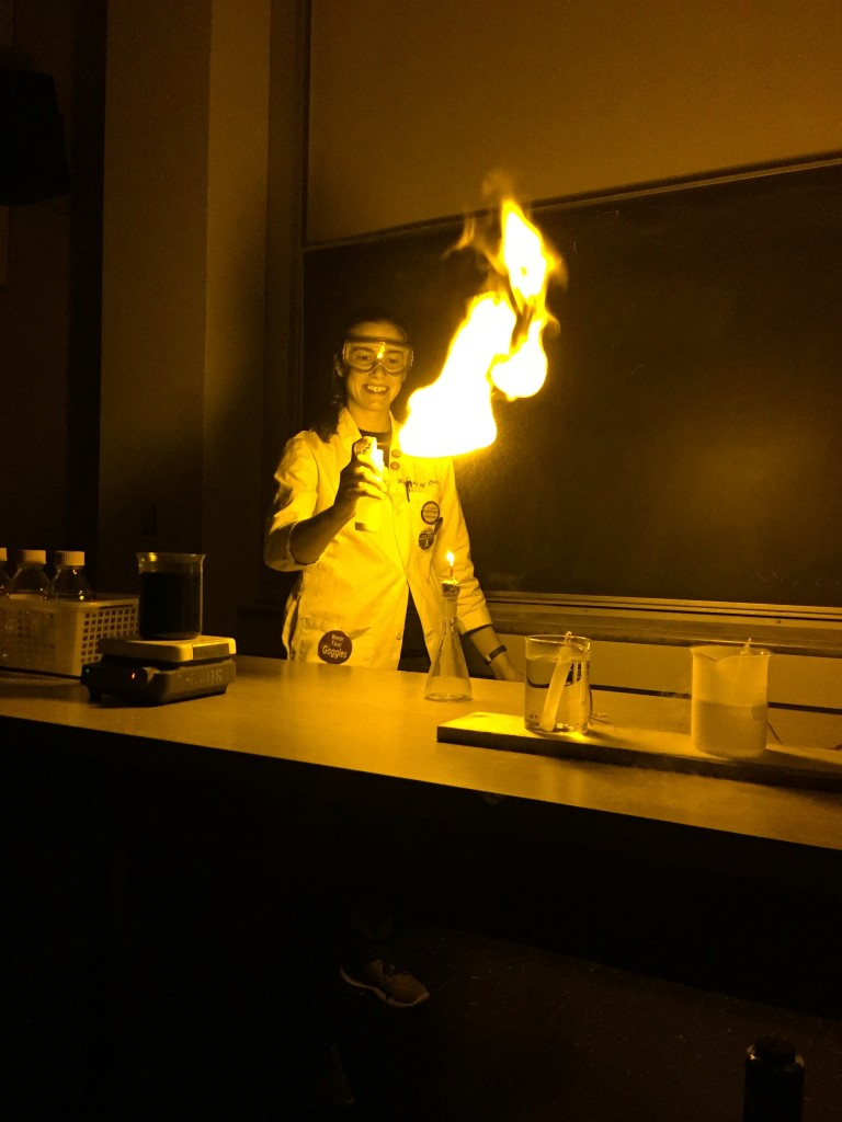 Loni plays with fire in front of an audience during a chemistry demo.