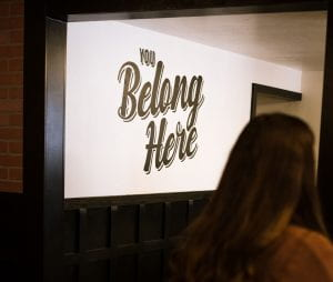 """person entering room with sign on wall, """"you belong here"""""""