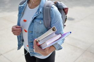 student holding books and binders