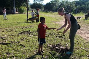UO student in Bolivia doing community cleanup work with indigenous child