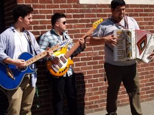 """(L-R) Cameron Marquez, Armando Lopez, and Jose """"Pepe"""" Contreras of Los Amigos de la Sierra playing Mexican norteño music outside the Hood River Public Library"""